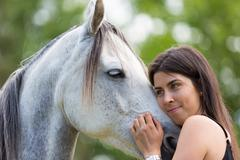 Young woman with her horse - stock photo