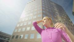 Attractive female runner stretching in the city before a run Stock Footage