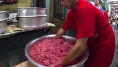 PHILIPPINES, ILO ILO - 30 MAY 2013: Asian man mixing sausage meat in metal bowl Stock Footage