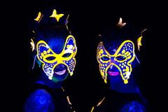 Photo of two women in luminous masks - stock photo