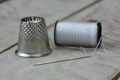 Sewing cotton needle and thimble - stock photo