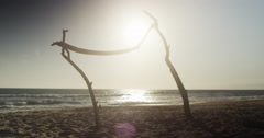 Wooden structure on beach looking out over sunset Stock Footage