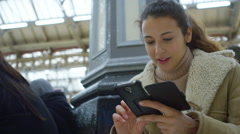 4k, young, attractive woman using an app on smart phone in a train station Stock Footage
