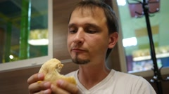 Guy greedily eating a burger in a fast food restaurant Stock Footage