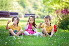 Three children in the park blowing soap bubbles and having fun Stock Photos