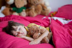 Sweet little boy, sleeping in the afternoon with his teddy bear - stock photo