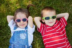 Sweel little boy and girl, wearing glasses, smiling, laying on the grass - stock photo