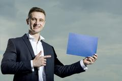 Muscular man in suit with sheet of paper Stock Photos