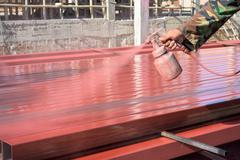 Spray red color to paint the steel of a building Stock Photos