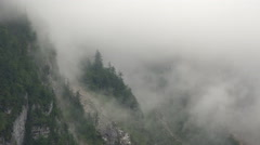 Clouds and fog timelapse at alps mountain wall forest Stock Footage