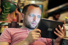 Young man watching film on tablet computer in trendy cafe NTSC Stock Footage
