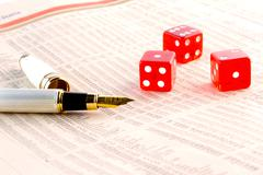 red dice and a golden pen  on the financial newspaper - stock photo