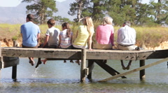 Rear View Of Multi-Generation Family Sitting On Jetty - stock footage