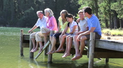 Multi-Generation Family Sitting On Wooden Jetty By Lake Stock Footage
