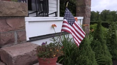 4K American Flag Waving in Breeze in Front of Quaint Stone Porch - stock footage