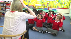 Pupils Copying Teacher's Actions Whilst Singing Song - stock footage