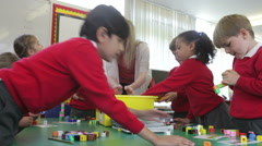 Pupils And Teacher Tidying Up Coloured Blocks - stock footage