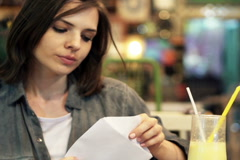 Sad, shocked woman reading letter with bad news in trendy cafe NTSC Stock Footage