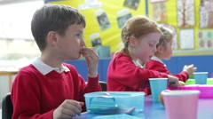 Schoolchildren Sitting At Table Eating Packed Lunch - stock footage