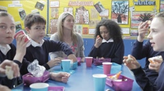 Schoolchildren Sitting Eating Packed Lunch With Teacher - stock footage