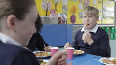Schoolchildren Sitting At Table Eating Lunch - stock footage