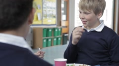 Schoolboy Sitting At Table Eating Lunch Stock Footage