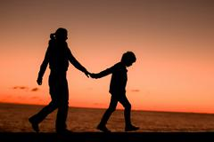Silhouette of a young mother and her son walking along a pier in front of a Stock Photos