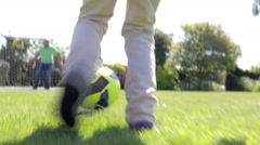Male Multi-Generation Family Playing Football In Garden Stock Footage