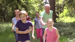 Multi-Generation Family Running Along Woodland Path Together Stock Footage