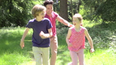 Father Chasing Children Along Woodland Path Stock Footage