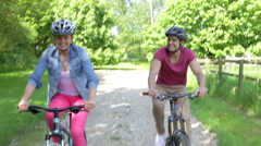 Couple Riding Mountain Bikes Along Country Track - stock footage