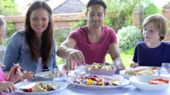Family Sitting Outdoors Around Table Eating - stock footage