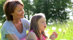 Grandmother And Granddaughter Blowing Dandelion In Field Stock Footage
