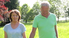 Senior Couple Walking Through Summer Field Together Stock Footage