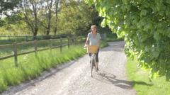 Senior Woman Riding Bike Along Country Track Stock Footage
