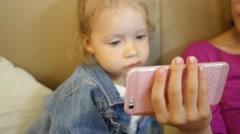 Little girl watching cartoons via smart phone display before go to sleep - stock footage