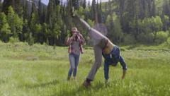 Girl Takes Smart Phone Video Of Boy Practicing Cartwheels In Mountain Meadow Stock Footage