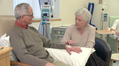 Senior Woman Sitting With Husband During Chemotherapy Treatment Stock Footage