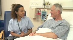 Nurse Sitting By Male Patient's Bed Using Digital Tablet - stock footage