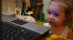 Little girl watching cartoons on laptop display at evening - stock footage