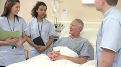 Medical Staff On Rounds Standing By Female Patient's Bed Stock Footage