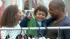 Family Looking At Clothes On Rail In Shopping Mall Stock Footage