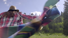 Free Spirited Girl Holds Up Blanket, Spins Around In Circle, In Mountain Meadow - stock footage