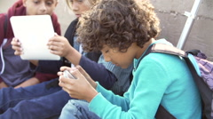 Young Boys Using Digital Tablets And Mobile Phones In Park Arkistovideo