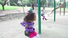 Slow Motion Sequence Of Four Young Girls Playing On Swings Stock Footage
