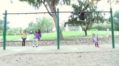 Slow Motion Sequence Of Four Young Girls Playing On Swings Arkistovideo