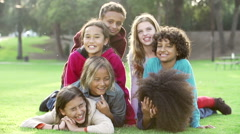 Group Of Children Lying On Grass Together In Park Stock Footage