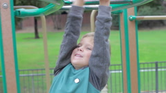 Young Boy Playing On Climbing Frame In Playground Stock Footage