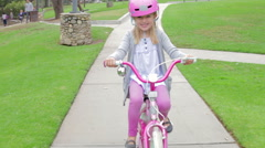 Young Girl Riding Bike In Park Looking At Camera - stock footage