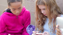 Young Girls Using Digital Tablets And Mobile Phones In Park Stock Footage